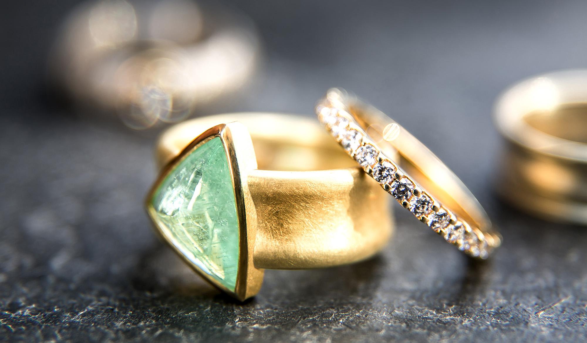 Angelika Hanstein Hamburg.Ringe in 750/000 Gold. Ring mit großem, gruenem, dreieckigem Paraiba-Turmalin. Daneben ein Memoire-Ring mit rundherum Brillanten. Im Hintergrund Eheringe.