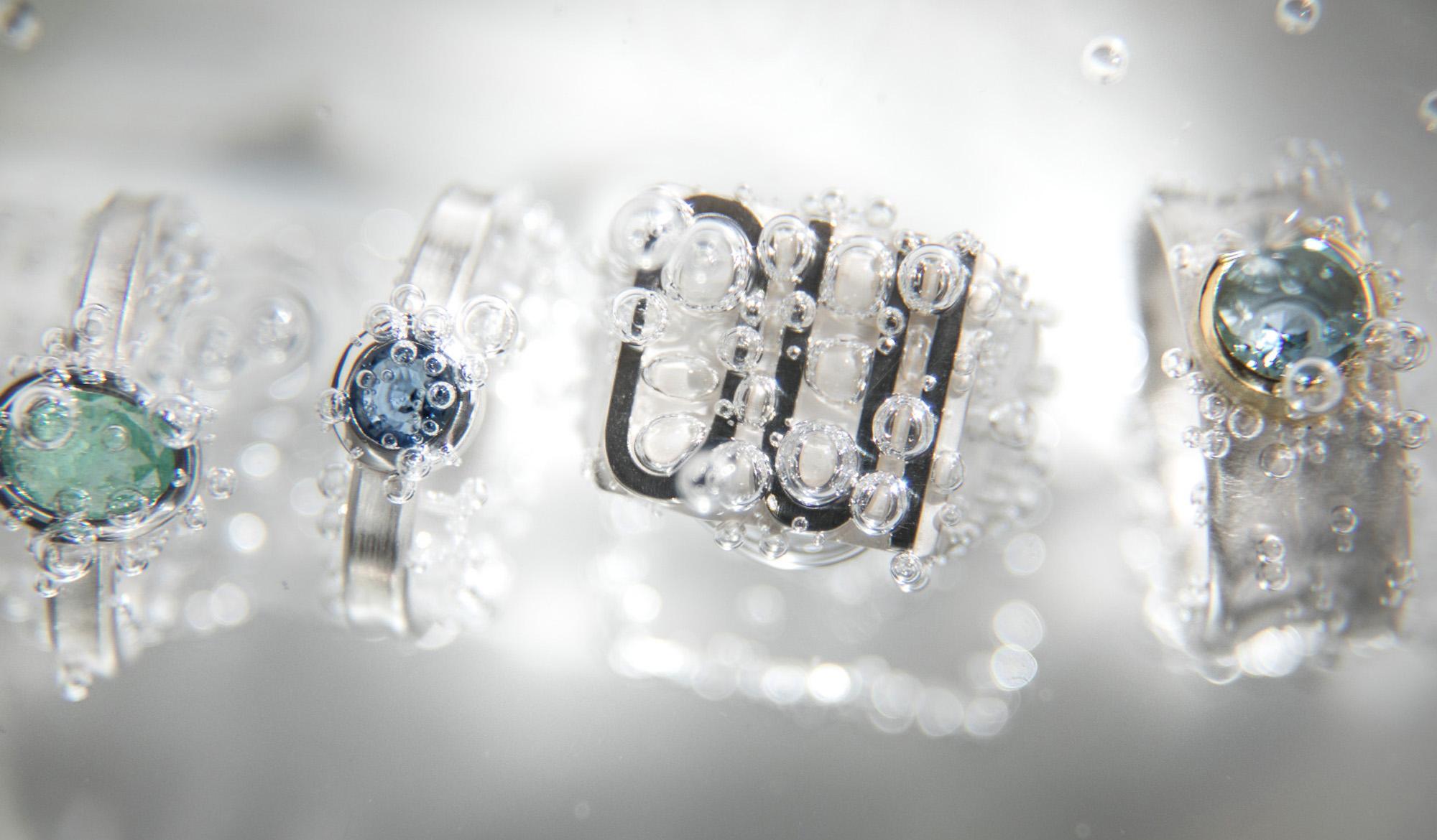 Angelika Hanstein Hamburg. Oui-Ring: Ringe in 925/000 Sterlingsilber mit hellgruenem Paraiba-Turmalin und kleinem blauen Saphir bzw. Safir. Rechts aussen ein großer, hellblauer Aquamarin.