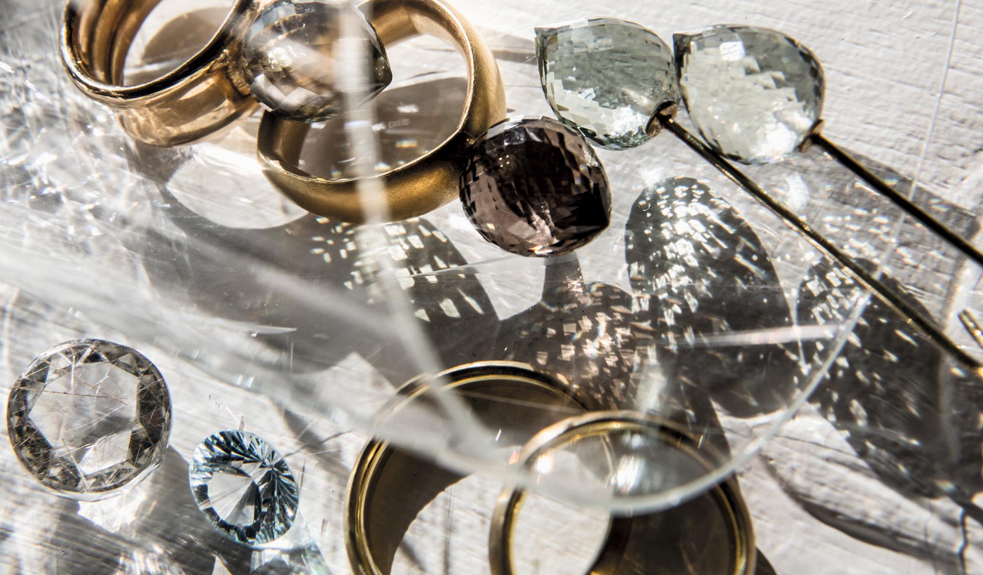 Angelika Hanstein Hamburg. Prasiolith-Ring 585/000 Roségold. Darunter ein dreieckiger Ring in 750/000 Gold mit einem Rauchquarz. Oben rechts Ohrschmuck in 585/000 Gold und Prasiolith. Unten links ein runder, facettierter hellblauer Aquamarin und ein runder facettierter Bergkristall mit Rutilnadeln.
